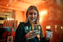 Woman Holding Cup Of Coffee And Smart Phone In Cafeteria. People And Work Concept. Coffee Shop.