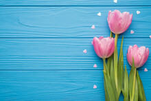 Photo Of Lovely Pastel Pink Tulips On Green Stems With White Glowing Confetti In Shape Of Hearts Around Lying On Bright Blue Table Desk With Blank Empty Space