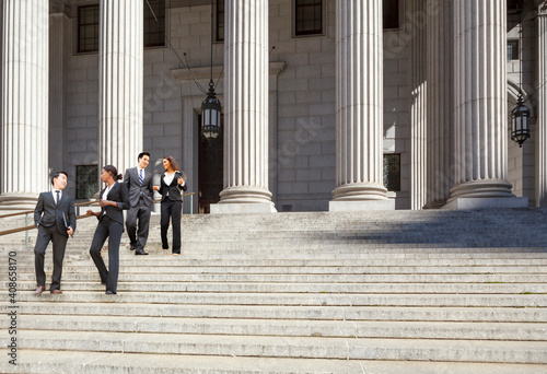 Canvastavla Four well dressed professionals walk down steps in discussion outside of a courthouse