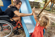 Mother In A Wheelchair Celebrating With Her Little Daughter In A Park