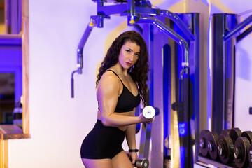 Fototapeta na wymiar Female athlete performing exercises with dumbbells in the gym