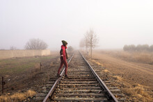 Side View Of A Girl Balancing On Train Rail While Walking
