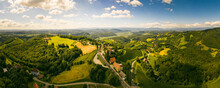 Aerial Panorama Of Of Green Hills And Vineyards With Mountains In Background. Austria Vineyards Landscape In Kitzeck Im Sausal