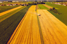 A Modern Combine Harvester Working On Wheat Field, Aerial View