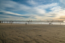 Sunset On Pismo Beach. Wide Sandy Beach, A Long Wooden Pier, Ocean View And Beautiful Cloudy Sky On Background