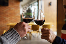Close Up On Hands Of Two Unknown Caucasian Men Holding Glasses With Red Wine Toasting - Man Cheers Celebrating While Holding Drink At Home Or Restaurant