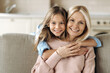 Portrait of a happy caucasian grandmother and granddaughter, or a mom with a daughter, they are hugging sitting on the sofa in the living room, smiling happily and looking at the camera
