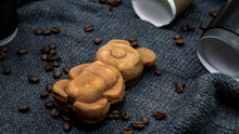 Background From Coffee And Pastries Teddy Bear, Aromatic Coffee With Pastries, Coffee Beans On Silk Cloth, Cappuccino In A Cozy Atmosphere..
