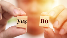 Yes Or No, Man Holding Two Wooden Cubes With Yes Or No Written On It, Making Decision