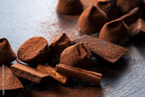 Fototapeta Cocoa powder, truffle chocolate and cinnamon on a stone plate obraz