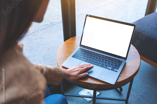 Mockup image of a woman using and touching on laptop touchpad with blank white desktop screen in cafe