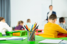 Pencils And Notebooks On Blurred Background Of Elementary School Students. High Quality Photo