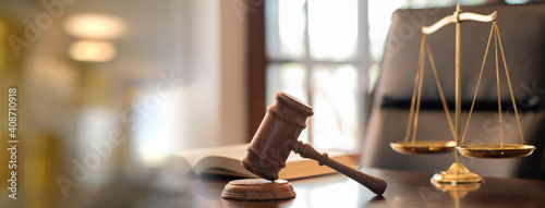 Fototapeta judge gavel, law books and scales of justice on desk in lawyer office