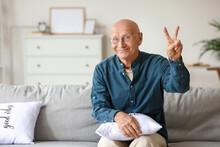 Senior Man Showing Victory Sign At Home
