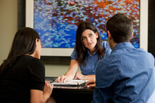 Female Real Estate Agent Talking To Potential Renters At Apartment Office