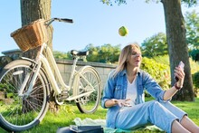 Happy Woman Sitting On The Grass Tossing Apple Making Video Call On Smartphone