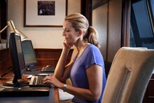 Woman Using Desktop Computer In Office On Cruise Ship