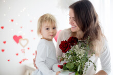 Cute Blonde Toddler Boy, Holding Box In Heart Shape And Flowers Giving Them To Mom