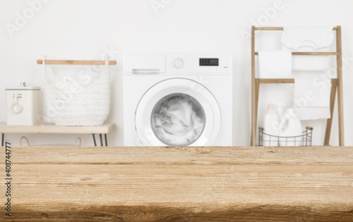 Fotografia Wooden table in front of washing machine loaded with laundry