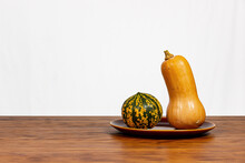 Still Life Of Two Pumpkins On An Earthenware Plate. Wood And White Background.
