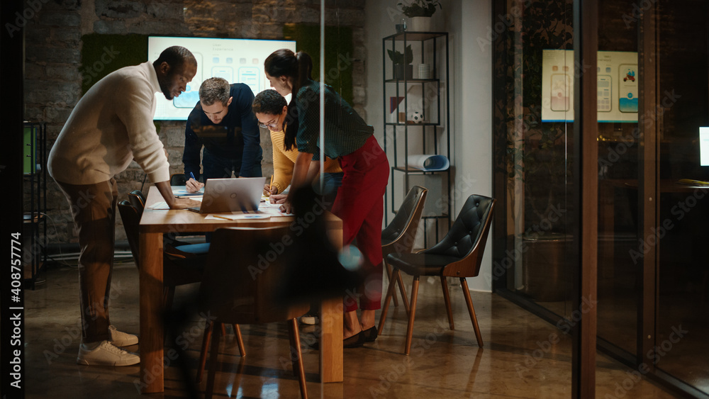 Fototapeta Diverse Multiethnic Team are Having a Conversation in a Meeting Room Behind Glass Walls in a Creative Office. Colleagues Lean On a Conference Table and Discuss Business, App User Interface and Design.