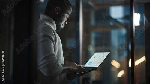 Fotografia, Obraz Handsome Black African American Male is Standing in Meeting Room Behind Glass Walls with Laptop Computer in an Creative Agency