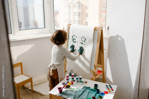 Photo Child painting her hand with paint and paintbrush