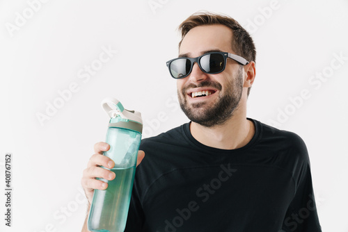 Fototapeta Happy young man in sunglasses smiling while drinking water