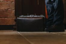 Leather Bag Stands On Ceramic Tiles On Floor