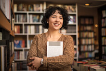 Woman In Library Holding Book.