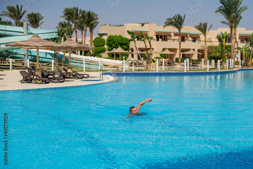 Photo handsome guy half-naked cheerful man smiling laughing in blue water swimming pool