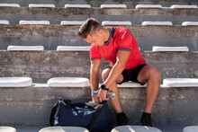 The Athlete Sitting In The Tribune Searches His Blue Bag Before Training During A Sunny Day