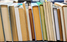 Row Of Many Old Used Books Displayed At Local Antiquarian Bookshop, Shallow Depth Of Field Photo, Only Few Pages In Focus