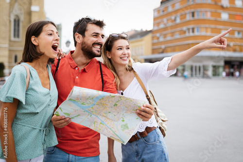 Happy traveling tourists sightseeing with map and having fun