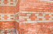 Old orange patterned brick wall. Wall texture.  Vintage texture. Brick wall corner. Alte orange gemusterte Backsteinmauer. Wandbeschaffenheit. Vintage Textur. Ziegelmauer Ecke.
