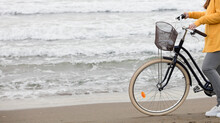 Woman With Bicycle And Yellow Sweater, Sea With Waves In The Background, Partial View, Space For Text.