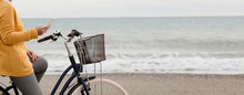 Partial View Of Woman In Yellow And Gray Clothes Riding Bicycle With Phone, Beach In Background