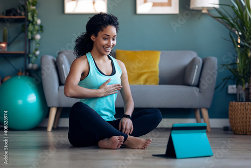 Photo Afro sporty young woman doing hypopressive exercises following online gym classes via digital tablet on floor in her living room at home