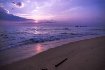 Fioletowo różowe niebo, krajobraz zachodzącego słońca na tle tropikalnej plaży i oceanu.