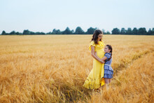 Happy Family: A Young Beautiful Pregnant Woman With Her Little Cute Daughter Walking In The Wheat Orange Field On A Sunny Summer Day. Parents And Kids Relationship. Nature In The Country.