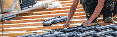 Fotografie, Obraz Process of laying the roof by burnt roof tile on the new building or house, buil