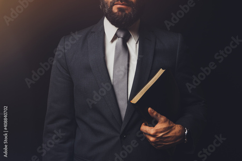 Cuadros en Lienzo man in suit holding a bible in his arm on a black background