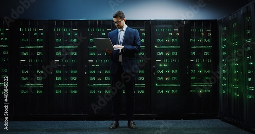 Canvas Print Young professional IT worker in suit standing in the middle of server room holding laptop and working with database