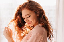 Merry Caucasian Girl Playing With Her Wavy Hair. Indoor Photo Of Stunning Lady Enjoying Photoshoot At Home.