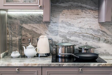 Cream Electric Kettle With Porcelain Tea Accessories On Granite Countertop Next To Ceramic Hob With Steel Pots And Pan