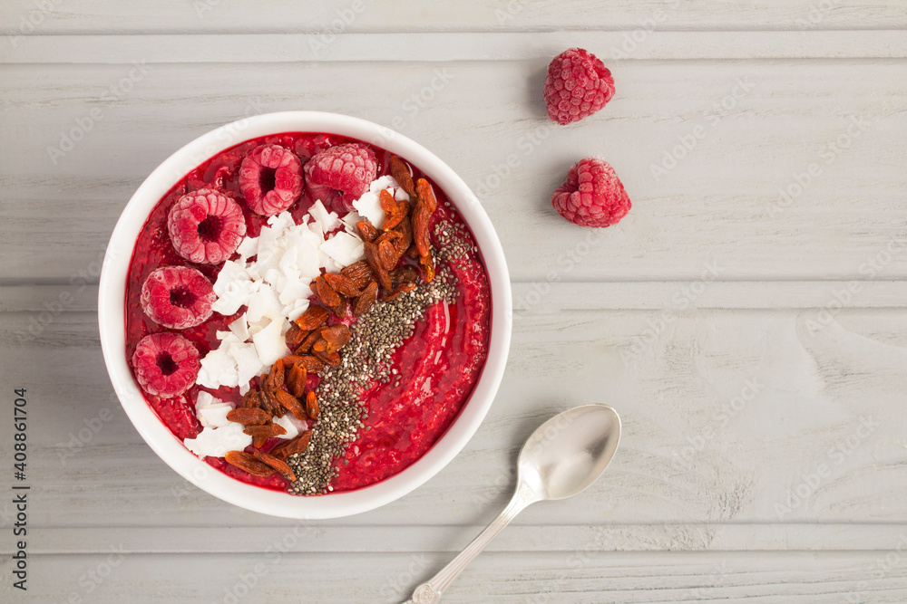 Fototapeta Top view of smoothies bowl with raspberries and natural superfoods on the gray background