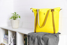 Yellow Felt Shopper Bag Against White Plank Wall Stands On White Chest Of Drawers. Nearby Lies A Gray Scarf Stole