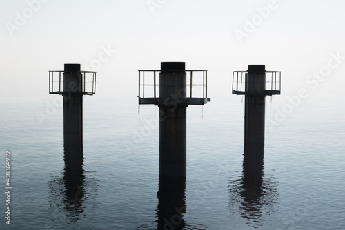 Fotografia, Obraz Three huge pillars of concrete emerge from the water against a strong diffused light, with reflections on water surface