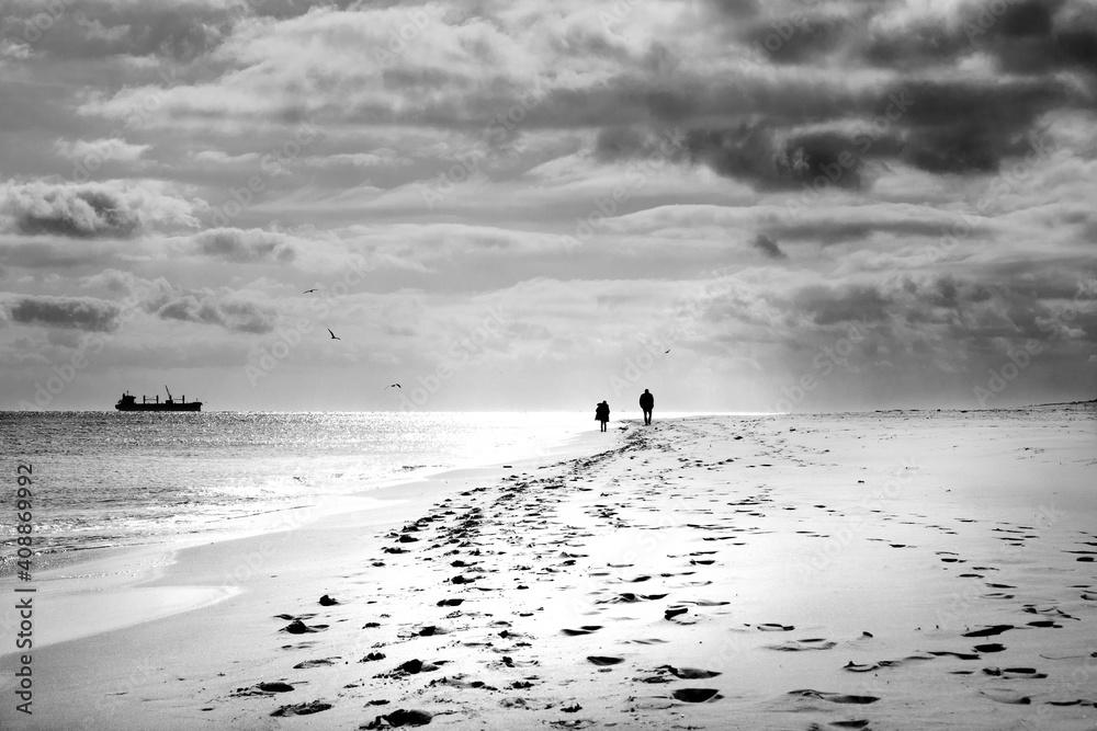 Fototapeta Szerokie ujęcie pod światło pary spacerującej brzegiem morza o zachodzie słońca, Hel nad Morzem Bałtyckim