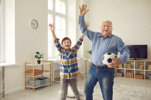 Obraz Excited grandfather and teen grandson enjoying free time, playing sports games together, having fun and celebrating victory of favorite soccer team. Happy childhood and active senior lifestyle concept - fototapety do salonu